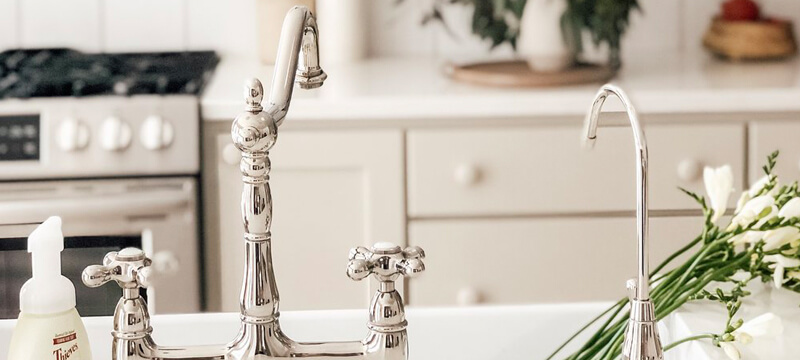A Polished Nickel Kitchen Faucet Seamlessly Fits a White Design